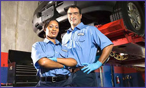 man and woman in blue auto shop uniforms